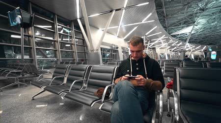 arrive : Traveler waits his flight at the waiting hall of the airport, man travels by air, man stares at the mobile phone screen, lonely passenger