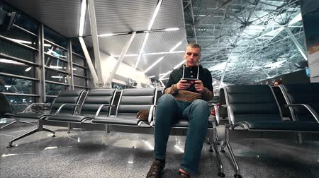 Traveler waits his flight at the waiting hall of the airport, man travels by air, man stares at the mobile phone screen, lonely passenger