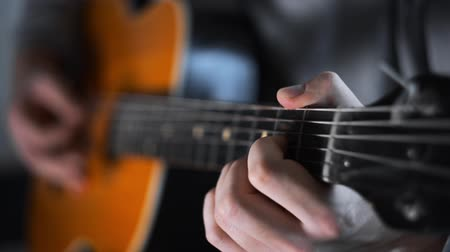 Guitar player plays random chords on the acoustic western guitar with steel strings ,exercises and arpeggios, video with sound, plaing the guitar,