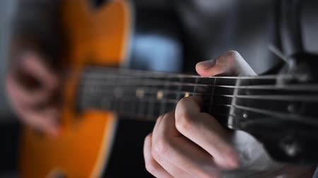 Guitar player plays random chords on the acoustic western guitar with steel strings ,exercises and arpeggios, video with sound, plaing the guitar Stok Video