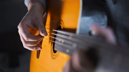 Guitar player plays scales and gamms on the acoustic western guitar with steel strings by finger picking technique, exercises and arpeggios, video with sound, plaing the guitar