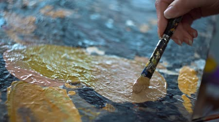 Artist mixes paints on the palette before painting a picture, painter at the studio, creator makes art