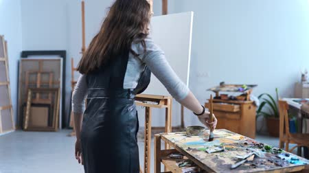 Artist paints a painting with passion in a studio, painter at work, creator makes piece of art, brushes and paints
