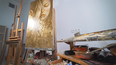 Oil painting on the easel at the artists work place, brushes and paints, palette with colors, workshop