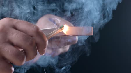 zapalovač : Man lights a match with fire, sparks and smoke in slow motion, ignition of fire, open fire, heat