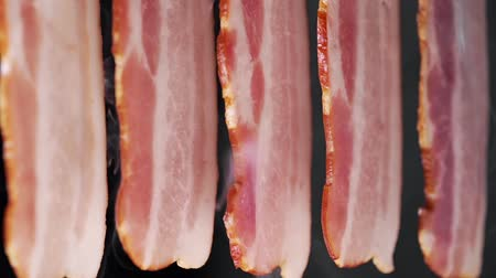 Smoked juicy and tasty bacon in the clouds of smoke on the black background, cooking meat, pork
