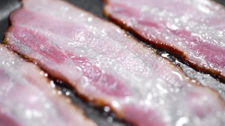 Pieces of tasty bacon is fried on the hot pan, hot boiling fat, cooking meat, meals with meat, bacon for breakfast