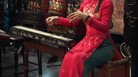 deerskin : Asian woman in national dress plays on the folk instruments of her country, folk music, instrumental ensemble, muscial people, folk music concert