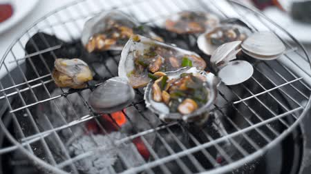 midye : Mussels is roasted in the sauce on the open fire of grill, cooking of shellfish outdoors, seafood barbecue, grilling the seafood Stok Video
