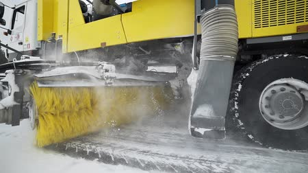 escorregadio : Heavy wheel machinery removes snow from the road with big massive rotating brush in the snowy weather, special machinery for roads cleaning, snow and ice removal Stock Footage