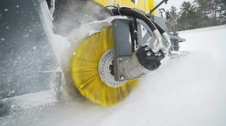 escorregadio : The yellow brush of snow and ice removal truck is rotating and removing snow from the road, wheeled harvesting machinery removes snow from the road with big massive rotating brush in the snowy weather, special machinery for road cleaning