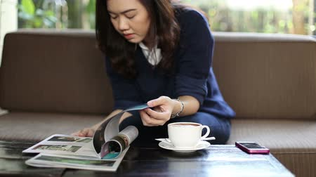 xícara de café : Asian beautiful woman sitting in coffee shop. Reading a book