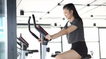 forcefulness : Young smiling woman wearing sport bra and using a exercise bike at the gym