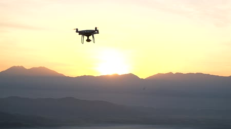 uav : Silhouette drone copter flying over mountain sky sunset, Vacation of nature landscape
