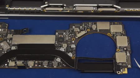 диагностировать : Disassembled laptop. Laptop motherboard next to the case, tools and tester. Close-up Стоковые видеозаписи
