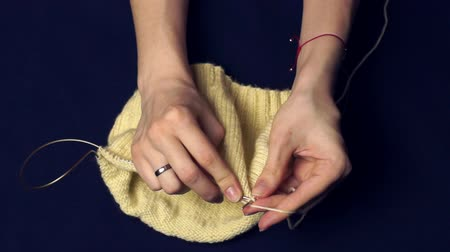 vyšívání : A woman knit with a light yellow yarn. Close-up on a darkblue background. Dostupné videozáznamy