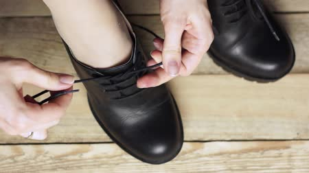 связать : Girl is tying a black boot. Wooden background. Стоковые видеозаписи