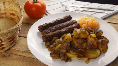 Serbian cevapi, cevapcici, Balkan minced meat kebab on a white plate with marinated cabbage Stockvideo
