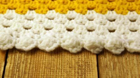 бежевый : Needlework. Colorful woolen bedspread crocheted on a wooden background. Close-up. Стоковые видеозаписи