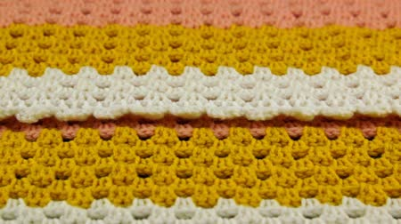 crochet : Needlework. Colorful woolen bedspread crocheted on a wooden background. Close-up. Stock Footage