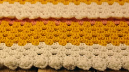 crochet : Needlework. Colorful woolen bedspread crocheted and three crochet hooks on a wooden background. Close-up.