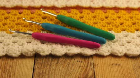 kézzel készített : Needlework. Three colored crochet hooks on a colorful crocheted woolen bedspread. Close-up. Stock mozgókép