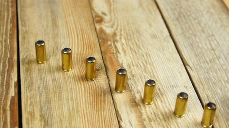 traumatic : Ammunition with rubber bullets next to traumatic pistol on a wooden background