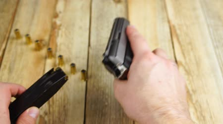 carregamento : Human insert magazine into the traumatic pistol on a wooden background.