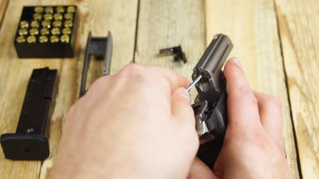 oco : Human cleans the barrel of a disassembled pistol on a wooden background.