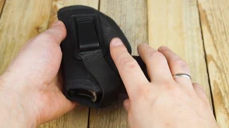 traumatic : Human inserts a pistol into a holster and pulls it out of a holster on a wooden background. Stock Footage