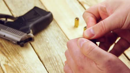 traumatic : Human inserts the ammunition in to pistol magazine on a wooden background.
