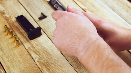 firearms : Human dismantles the pistol for maintenance and cleaning on a wooden background. Stock Footage