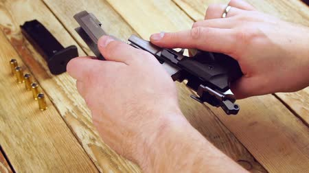 traumatic : Human collects the pistol after maintenance and cleaning on a wooden background.