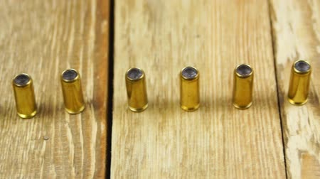 traumatic : Ammunition with rubber bullets for traumatic pistol on a wooden background Stock Footage