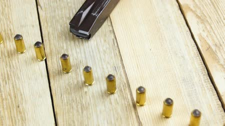 traumatic : Ammunition with rubber bullets next to traumatic pistol and ammunition magazine on a wooden background Stock Footage