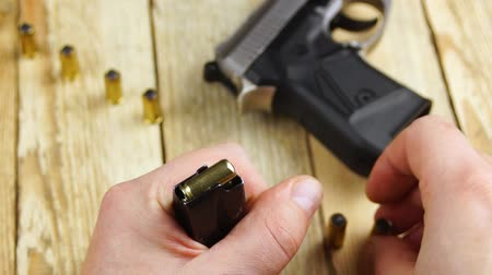 traumatic : Human pulls out the ammunition of a pistol magazine on a wooden background.