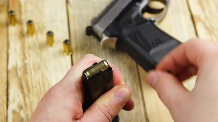 titular : Human inserts the ammunition in to pistol magazine and inserts the magazine into the gun on a wooden background. Stock Footage