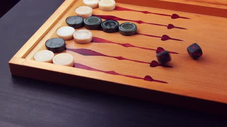 Backgammon game. Human rolls the dice on the backgammon board against the background of checkers. Close-up Wideo