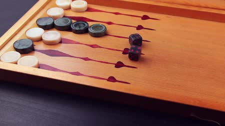şanslı : Backgammon game. Human rolls the dice on the backgammon board against the background of checkers. Close-up Stok Video