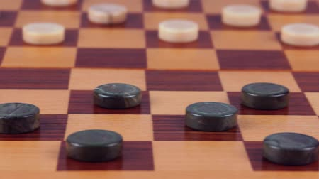 Malachite checkers and marble checkers on a wooden checkerboard. Close-up Wideo