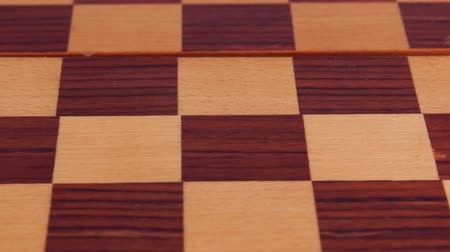 Two marble checkers on a wooden checkerboard. Close-up Stock Footage