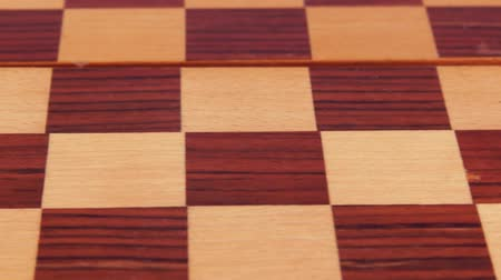 Malachite checker and marble checker on a wooden checkerboard. Close-up