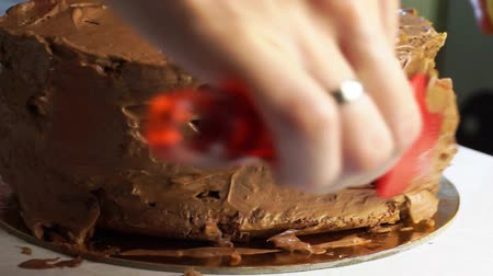 Cooking homemade cake. The pastry chef spreads a layer of chocolate cream on a biscuit using a red pastry shovel. Close-up Stock Footage
