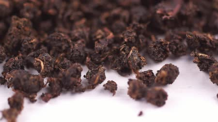 kurutulmuş : Fermented copory tea. Dried leaves of fireweed. Macro video of a dry tea mass on a white background