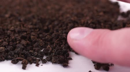 kwiaty polne : Fermented copory tea. Dried leaves of fireweed. Macro video of a dry tea mass on a white background. Human aligns tea mass with his finger. Close-up