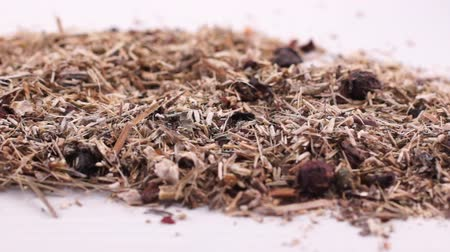 Herbal collection for the preparation of a tonic drink. Dry herbal mass lies on a white background. Close-up Wideo