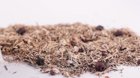 Herbal collection for the preparation of a tonic drink. Dry herbal mass lies on a white background next to three tea bags. Close-up