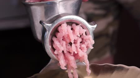Cooking minced meat with a manual meat grinder. Close-up of front part of mincing-machine with mincemeat in. Showing the forcemeat process.