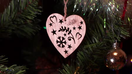 prase : New Years composition, Christmas decorations. Christmas toy in the form of a wooden heart hangs on a decorated Christmas tree on the background of a blinking garland and other toys. Close-up