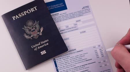 Man fills out a customs declaration form next to an American passport on a white background. Close-up